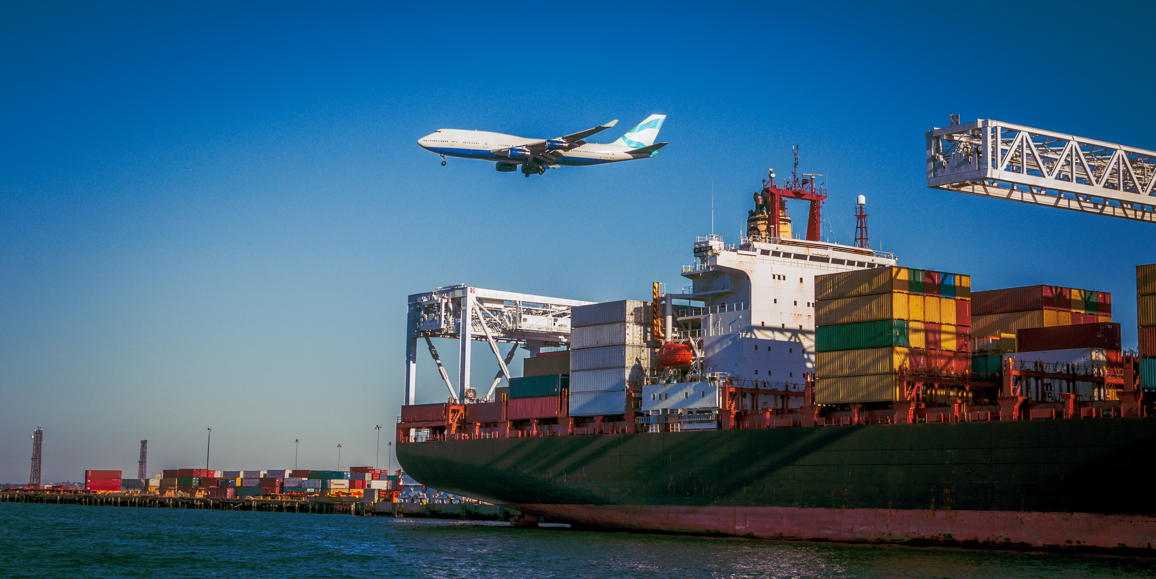 Photo showing a container ship at the port and an airplane in the sky